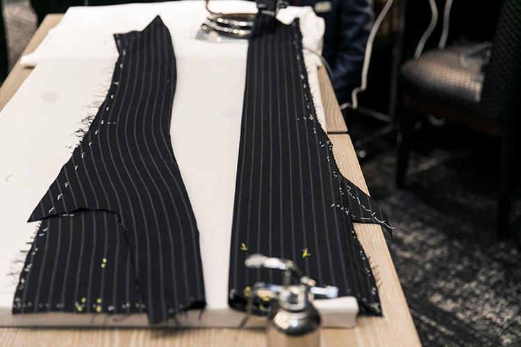 右がアイロン前の平面的なストライプ柄、左はアイロンをかけて立体化させた後のストライプ柄。かなりラインも変わって身体の線に沿った形になったことが分かる。生地を縫う前の段階でこうした手間をかけることにより、身体にぴったりフィットした着心地のスーツを作ることが出来る。