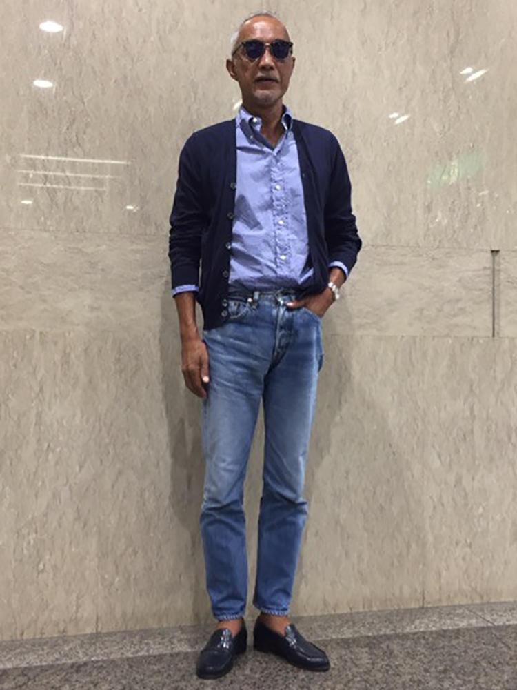 ブルーのBDシャツにハイゲージのカーディガン、ジーンズ。サングラスと日焼け肌が男っぽさをプラスしている。
