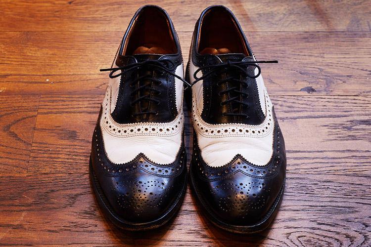 アレンエドモンズのコンビシューズ。「私自身を表している一足。自分ならアメリカ靴も英国っぽく見せられると思っています。ネイビーのスーツに白やエナメルだとやりすぎかな。コンビだとグレンチェックのスーツに合うし、ブローグが装いの崩しとして有効です」。