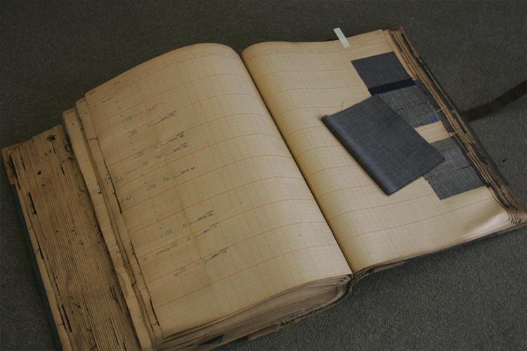 スーツの生地は、写真のエドウィーンウッドハウスのアーカイブの生地見本のなかから選んだものを復刻。