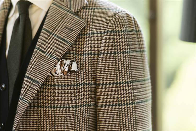 落ち着いたブラウン系チェックのジャケットに、同系色のチーフを挿して。