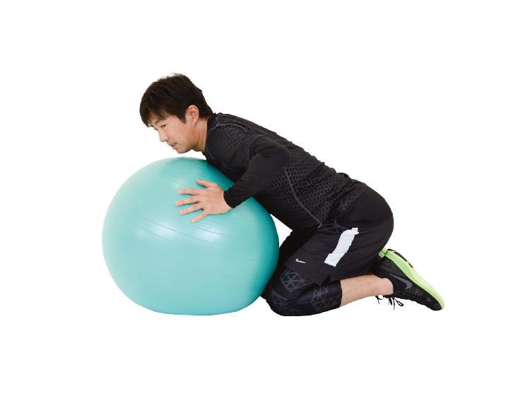 <b>1. ボールにくっついて座る</b><br>バランスボールを抱えるようにして座る。両手でボールを押さえておく。