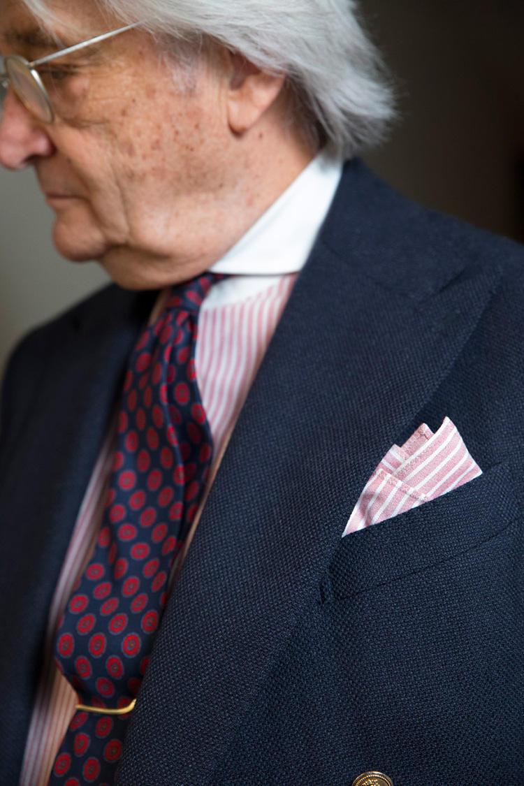 シャツは淡いピンクトーンのストライプで、襟がクレリックだから、あまりパンツと喧嘩しない。対してネクタイは、ネイビー×赤なのでジャケットとも美しくリンク。シャツと共地のチーフを合わせる鉄板テクニックも、もちろん健在!