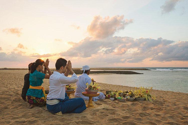 インド洋を目の前に、バリ島南部のヌゥサドゥアエリアに位置するザ・リッツ・カールトンバリ。時間に追われることのない、心地よい滞在とサービスを体感できる。写真は、朝7時からマンクー(司祭)と1時間ほど行う魂の浄化儀式。太陽や海の神々に祈りを捧げ、悪い気を祓う。