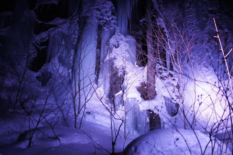 夜の奥入瀬渓流を専用車がライトアップ。雪と氷壁に光が当たり、昼間とは違った独特の妖しさを描き出す。