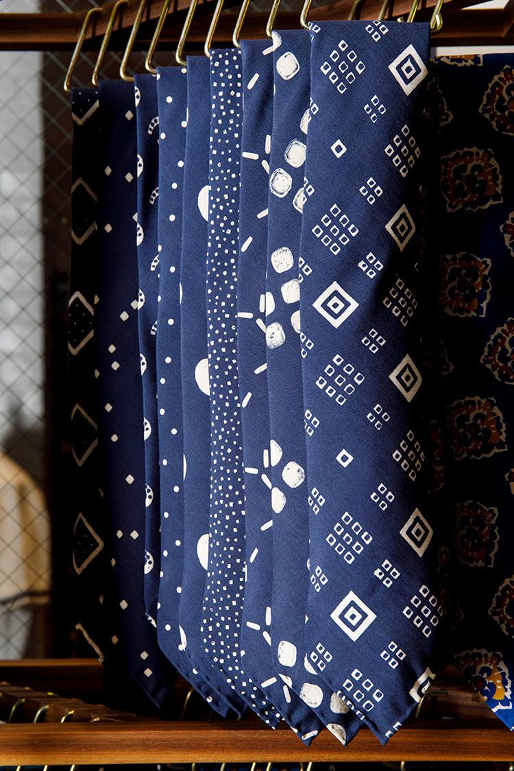 少し濃度の浅いネイビーに、かすれたような幾何学柄。紺ジャケに白シャツ、サックスシャツなど夏のブルートーンコーデに映えること間違いなし。