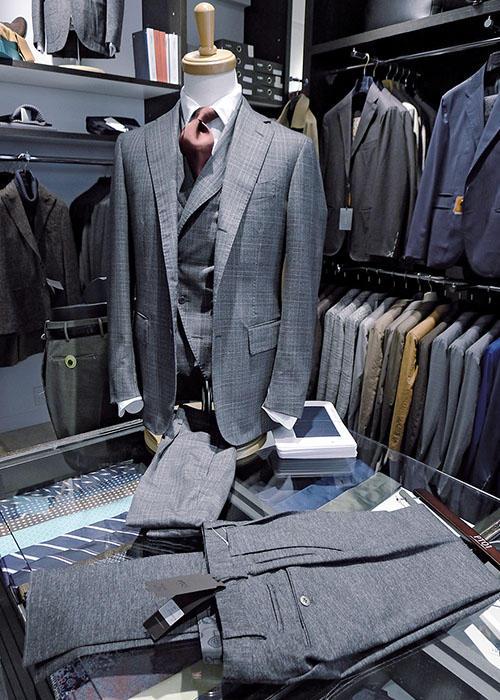 最初にクラシックを手掛けた店舗が、現在の「ブルック」。「スティレ ラティーノ」のスーツに、変則的なダブルのベスト合わせ、スリーピースで提案するのは「ブルック」独自のアイデアだ。手前のパンツはジャージー素材による「PT01」トラベラー。