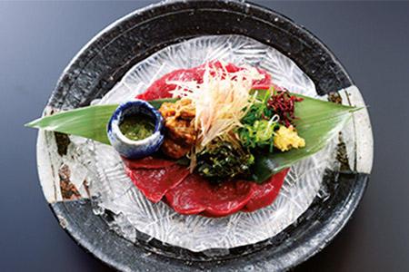 夕食は館主の独創性が光る料理が満載。辛味噌や薬味などを巻いて味わう名物の馬刺しは最高の酒のアテ。