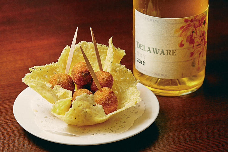 <b>凝縮感と香り豊かな味わいには多少のコクも合う</b><hr>デラウェアやコンコードなど食用ぶどうを使った日本ワインも近年増えている。ダイヤモンド酒造 デラウェア ドライ2016(2800円)には「チーズの籠に乗せた肉詰めオリーブのフリット」(750円)を。果実の凝縮感があり、アロマティックな香りゆえに、前菜系の肉料理や豚肉のパテなど少しコクのある料理とも相性は良い。