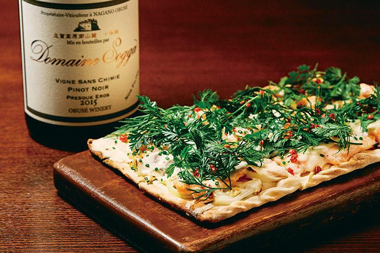 <b>ワインの香りに合わせてハーブで香り付け</b><hr>小布施ワイナリー ドメーヌ・ソガ ピノ・ノワール フレスク・エロス2015(6400円)は、ロゼっぽい色味で梅しそのような味わいと香りが楽しめる。味の骨格もあるので、「ハーブたっぷり!サーモンとサワークリームのタルト・フランベ」(1350円)のようなサーモン、付け合わせのハーブやピンクペッパーにも負けない。
