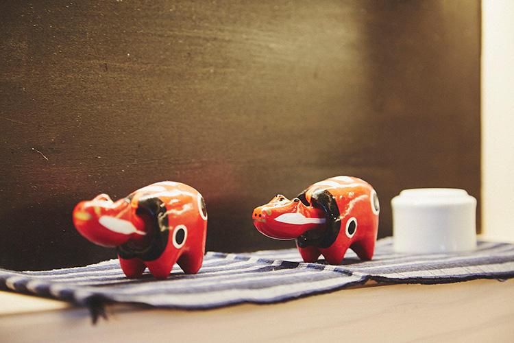 赤べこは、全身が赤く、白い縁取りのある黒い斑点が特徴。赤い色が病魔を払うと言われ、また、赤べこの斑点は本来、子供などがかかる疱瘡を表したもので、牛が子供の身代わりになったといわれる。これらの赤べこは、お土産ショップでも販売。