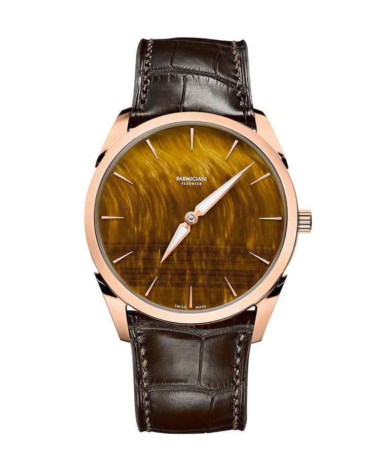 <b>PARMIGIANI FLEURIER</b> パルミジャーニ・フルリエ トンダ 1950<hr style='margin-bottom:20px'><b>天然石で一層際立つ黄金比による造形美</b></br>金褐色に煌めく細かな縞模様を浮かべるダイヤルは、天然石のタイガーズアイ製。ダイヤルもケースも、すべてのディテールは黄金比に基づいて設計される。極めて美しい外装に包まれたマイクロローターによる薄型自動巻きも、職人の手業で美観を極めている。限定50本。自動巻き。径39mm。18KRGケース。アリゲーターストラップ。305万円(パルミジャーニ・フルリエ)