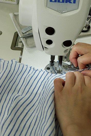すそ部分の三巻縫い。ミシンで曲線をスムースに縫い上げる技術は圧巻。かつて、'シャツづくりの花形'と呼ばれたパートである。