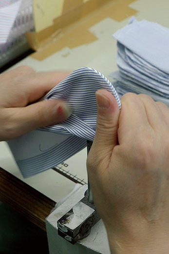 <b>Nice Detail!</b><hr style='margin-bottom:20px'>生地と芯地を縫い合わせたカフは、専用の作業台を使い手仕事で1枚1枚表面にひっくり返していく。