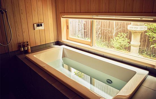 心地よい香りの檜張りの浴室からも庭が眺められ、四季折々楽しめる。