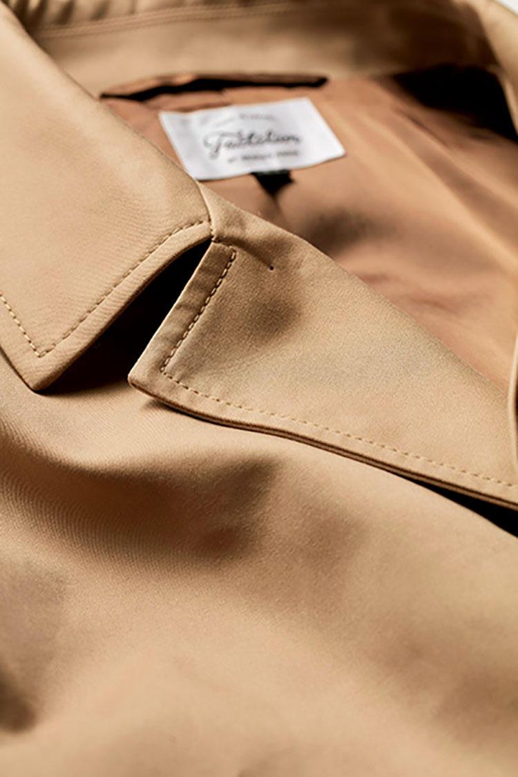 <b>高密度に織られた素材感の美しさ</b></br>糸の段階で染められた先染め糸を高密度で織りあげ、美しい光沢感を実現。ミニマルな比翼仕立てもあいまって、美しいコートが完成。コート5万5000円/ファクトリエ(ファクトリエ 銀座フィッティングスペース)