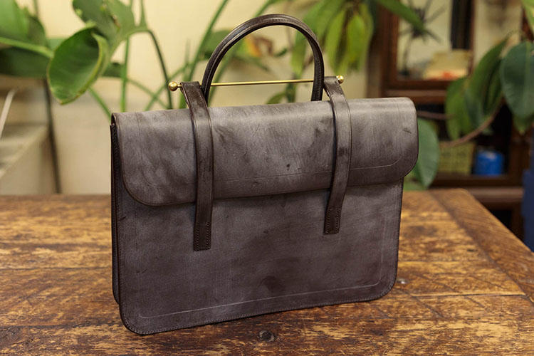 「ミュージックバッグ」<br>イギリスの音楽学校の学生が楽譜を入れて持ち歩いたバッグが原型と言われ、スコア(楽譜)バッグとも呼ばれている。真鍮のバーを、もう一方のハンドルに引っかけることにより蓋を固定する独自の構造は必見。素材はイングリッシュブライドルレザー。5万5000円