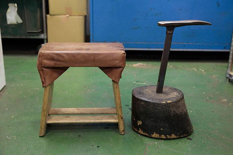 コンパクトな作業用の椅子と靴を固定する金属の作業台。