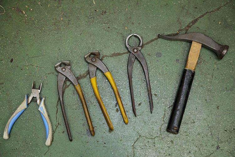 作業道具。左からニッパ—、くい切り2点、ピンサー、ハンマー。くい切りは釘の頭を切るためのもので、ピンサーは釘を引き抜くときに使われる。