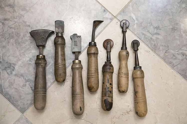 ソールとヒールをキレイに仕上げ、飾りを型押しする作業に、これだけの道具が必要とされる。