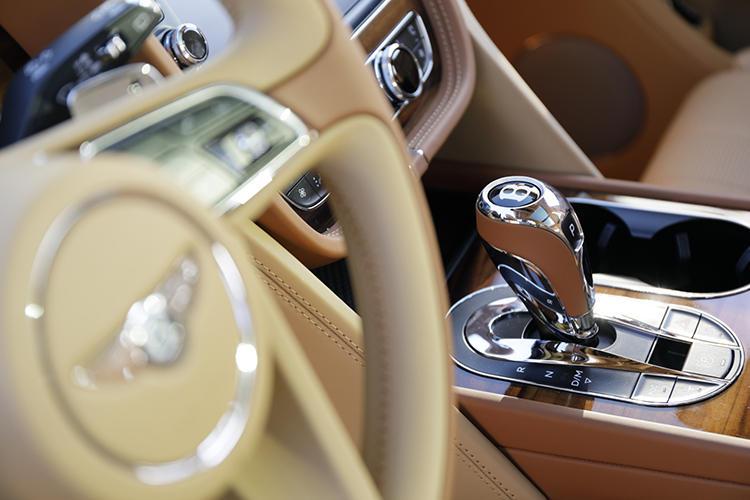 左右対称にこだわったダッシュボードまわり。取材車は左ハンドル車で、右ハンドル車ではA/Tセレクターとカップホルダーの左右がそっくり入れ替わる。金属パーツの多くは手作業で丁寧に仕上げられているのだそうで、深みのあるメッキの光沢が贅沢だ。回転ツマミの周囲にはベントレー伝統のローレット加工も施されている。
