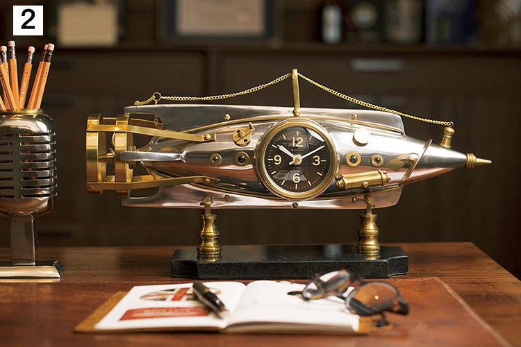 """<b>趣味の小物に囲まれて仕事の空間も心地よく</b><br><br>アンティーク好きな遠藤さんのデスクにフィットする米国インテリアブランド「ペンデュラックス」の小物。古い潜水艦や飛行機の計器を模したアンティーク調のデザイン時計が人気。真鍮製の卓上時計は、1902年頃のフランスの魚雷から想を得たもの。""""ノーティラス""""6万2000円(パフ コレクション)"""