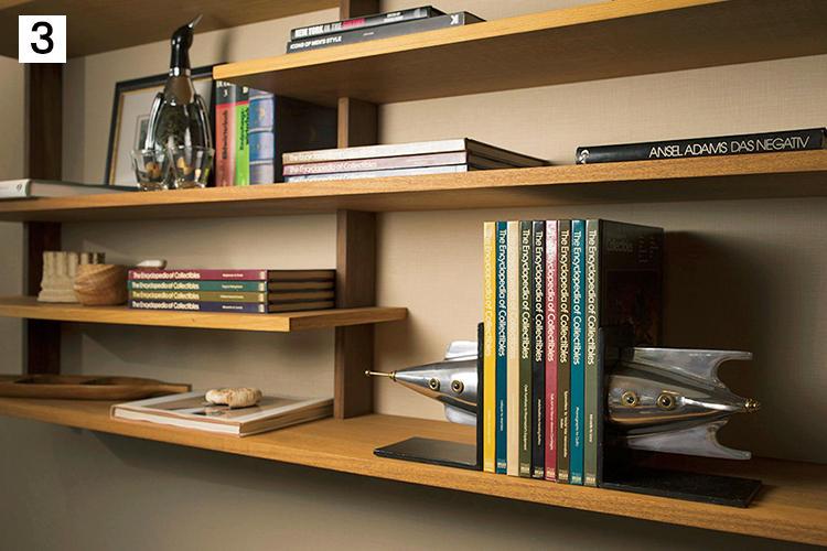 <b>旅先の思い出や本も立派なインテリアに</b><br><br>本棚には、『Collector's Encyclopedia』シリーズや、アンセル・アダムスの写真集など。遠藤さんが気に入っているペンデュラックスのブックエンドと共に。左のペンギンはデキャンタで、イギリスの蚤の市で見つけたもの。大量のコレクションから、時折入れ替えも。
