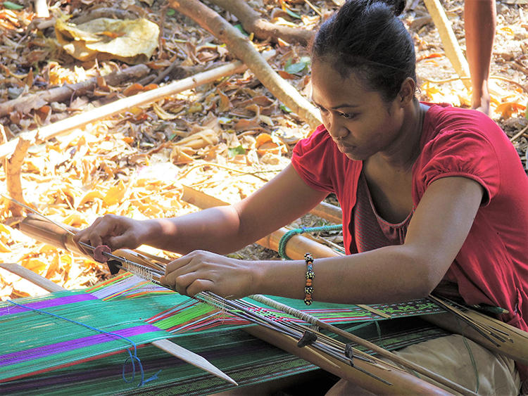 伝統工芸である織物(イカット)を手織りしている様子