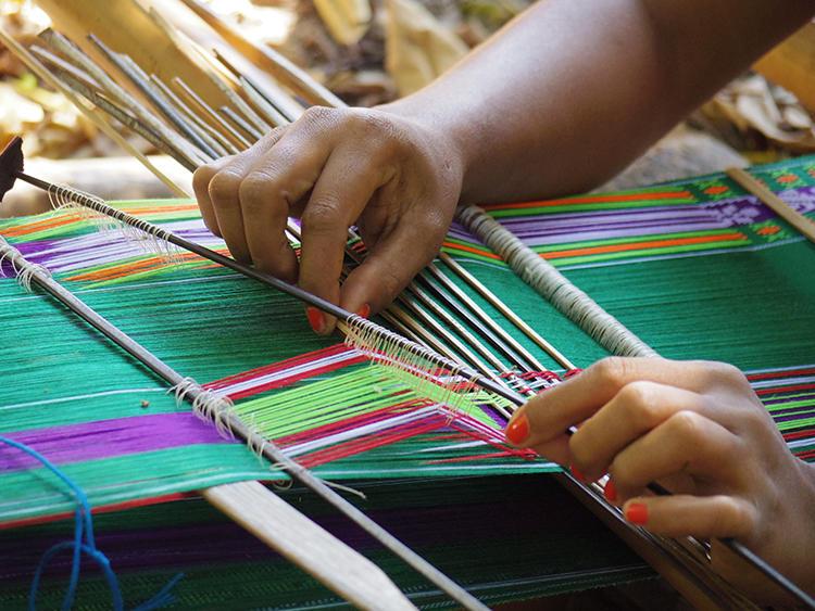複雑に串を使いながら織物を織りあげる様子。