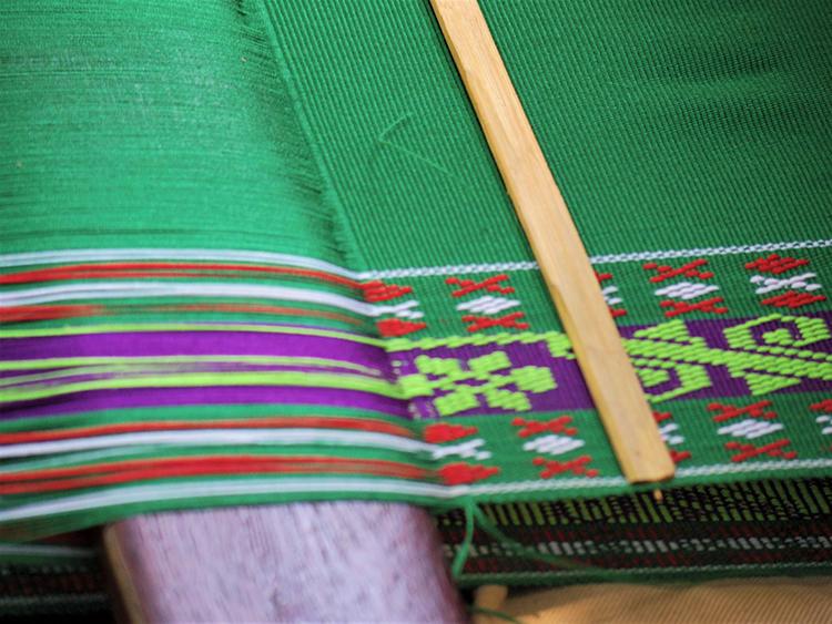 緯糸を複雑に通して、細かく柄を織りあげていく。