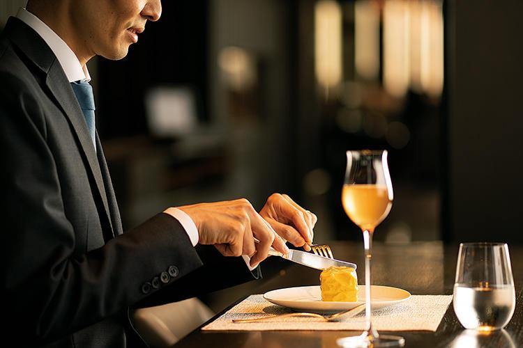 <b>1日10組限定</b><hr>鮮やかな黄色のチョコレートを割ると、上からキャラメルシナモンのムース、ジンジャーリキュールやライムゼストで香りをつけたパイナップルのコンポート、アーモンドスポンジ、スパイシークランチービスケットが層に。1個1100円。ホテル自家製ベルモット1900円を添えるとより魅力的に。