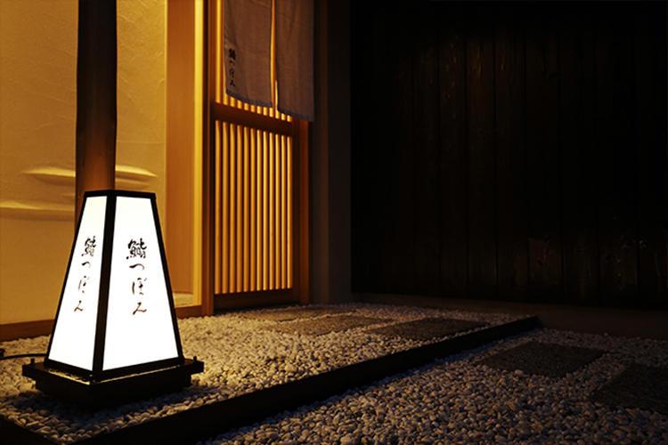 東京・中目黒の閑静な住宅街の一角に位置。きりっとした白暖簾と行燈が店の存在を告げている。