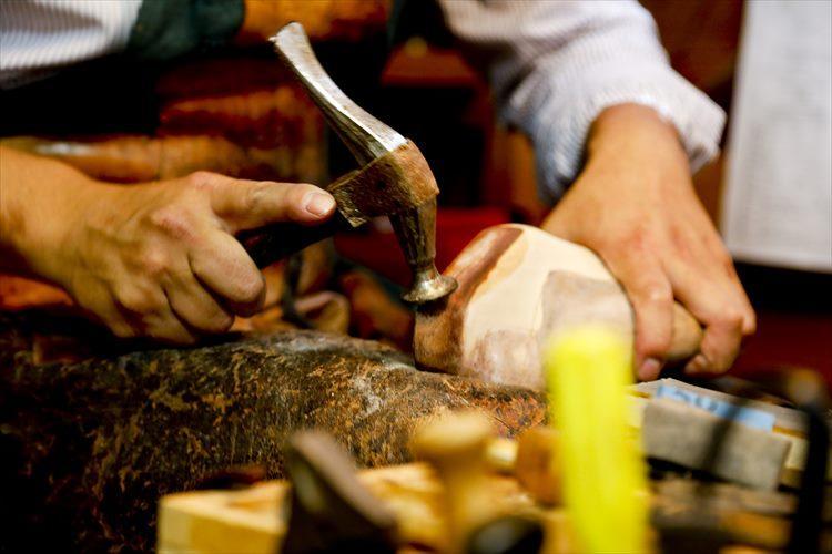 ハンマーでヒールの形を整えていく。木型は水を付けて革を乗せて叩き厚みの調整をして行く。