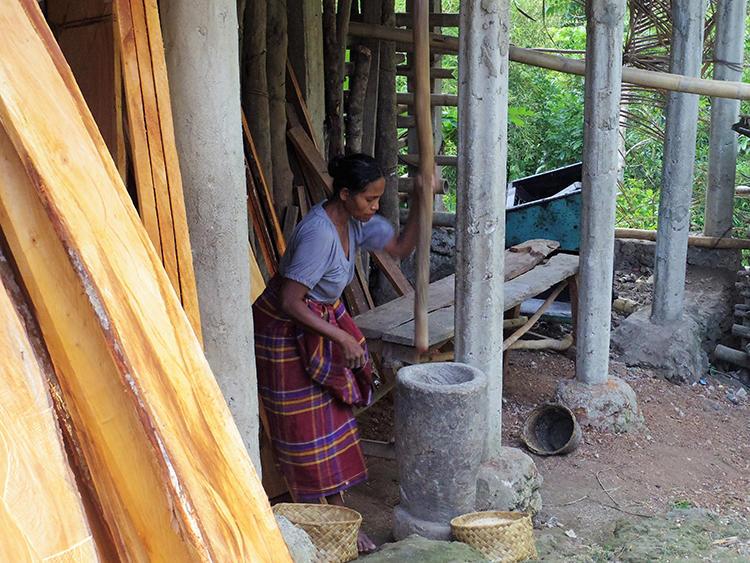 臼に入れたお米を木の棒で突いて脱穀をしている村の女性。
