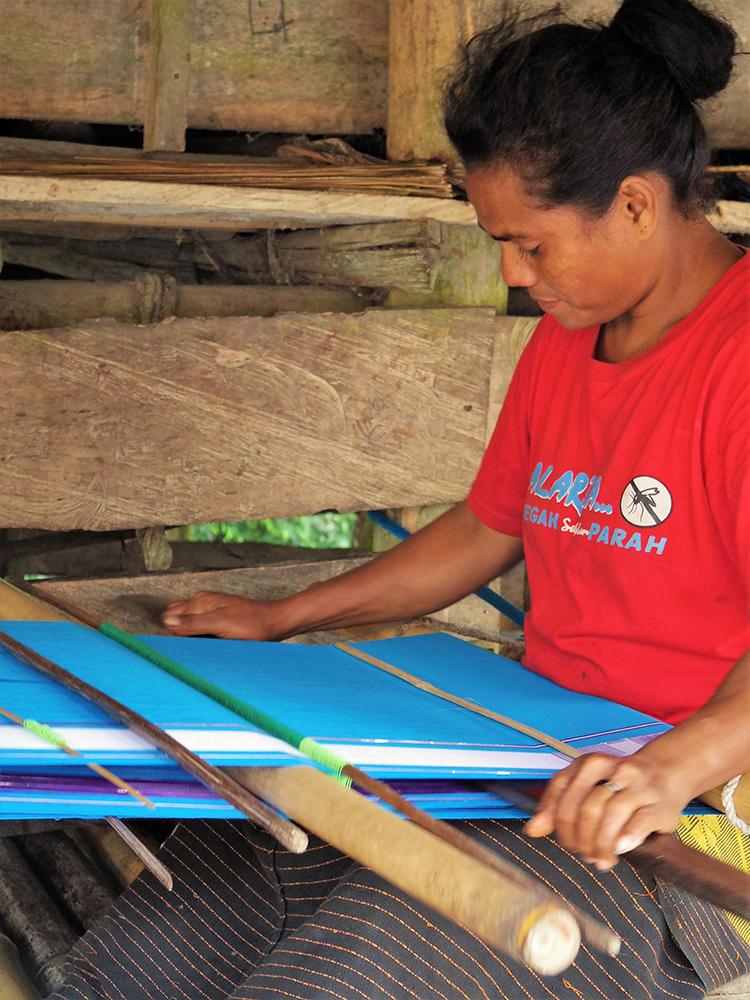 村の女性が伝統的な絣織物、イカットを織っていた。