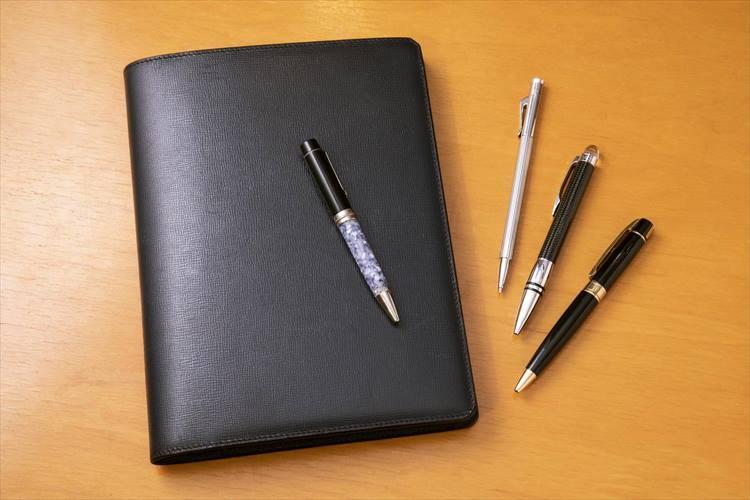 手帳はミラノのヴァレクストラで購入したカバーに、中身はクオバディスを愛用。(左から)ペンはデルタ、ファーバーカステル、モンブラン、シェーファー。「店頭でお客様にお使いいただく場合に備え、ペンは2本必要。デジタル製品は電池が切れると、仕事ができなくなります。だから、スケジュール管理は紙が基本。出張でスケジュールが詰まっていると、充電をしているヒマなんてありません」。