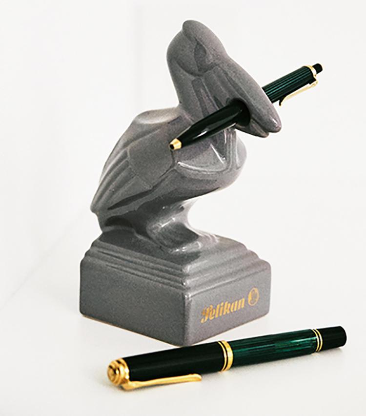 <b>PELIKAN<br />ペリカンのペン置き、ボールペン(上)、万年筆(下)</b><br />ペンと万年筆は独の高級筆記具メーカー、ペリカンを愛用。店頭ディスプレイ用と思われる非売品のペン置きは、奥様が某書店のアンティーク文具フェアで一目惚れして購入されたもの。