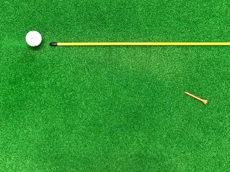 飛球線後方の右内側に目印となるものを置きます。目印にはティやコインなどの高さのないものを使用しましょう。写真では飛球線後方の延長線が分かりやすいようにイエローの棒を置いてありなす