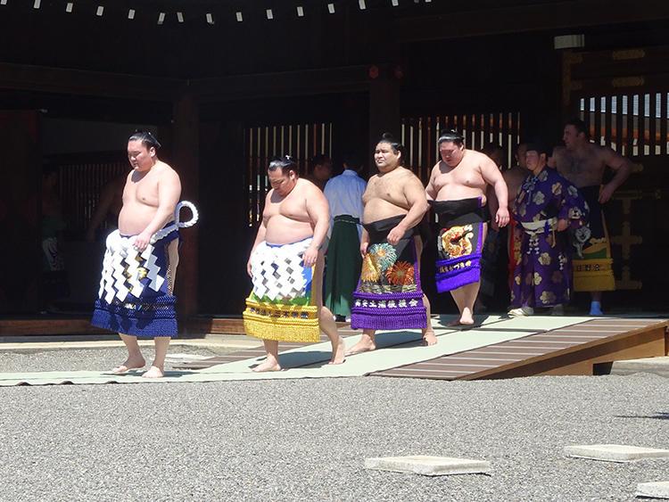 横綱・白鵬を筆頭に化粧まわしを締めた幕内力士たちが本殿に向かいます