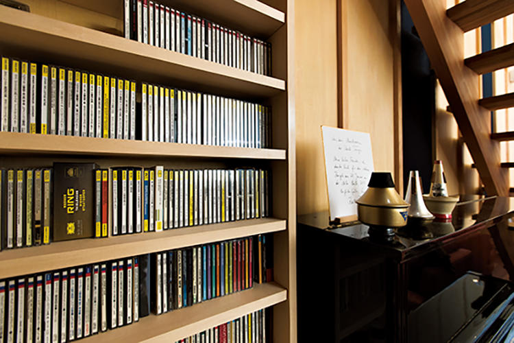 階段下の造作棚にはCDがずらりと並ぶ。ピアノの上にはトランペットのミュートが。