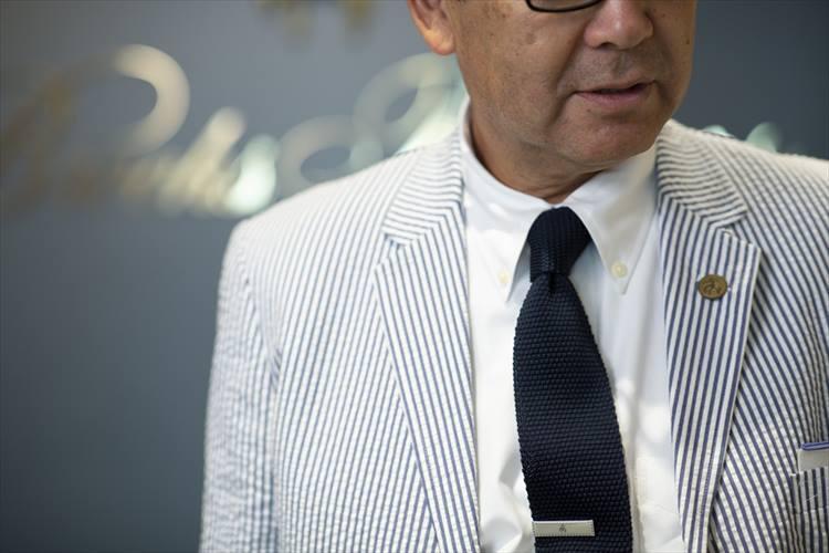 ボタンダウンシャツに合わせたニットタイが、シアサッカースーツの軽やかさをさらに高める。