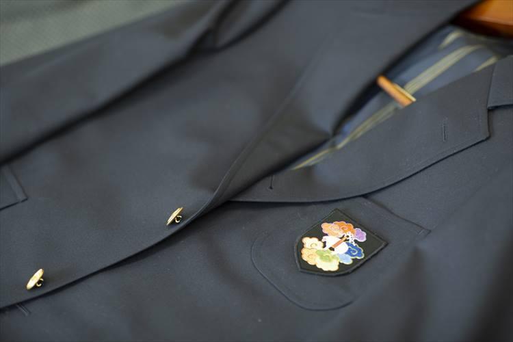胸には刺繍作家の長艸敏明(ながくさとしあき)さんが手掛けたワッペンが取り付けられている。イベントでは、このほかにも、長艸さんが刺しゅうを施したネクタイなども登場した。