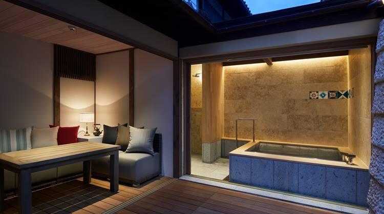 琉球石灰岩に囲まれた浴室は窓を開ければオープンスペースと一続きになる。広い浴室に設置された十和田石の大きな浴槽には、ヒバの広い縁が付いていて、優雅なことこのうえない。浴槽脇には頭上、ハンド、横方向と3タイプのシャワーを完備している。ⒸNakasa&Partners