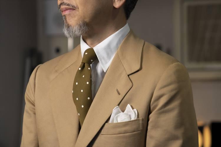 同系色でまとめたスーツとネクタイが品のよさを感じさせる。リネンの白チーフからは清潔感が漂う。