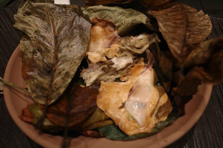 <strong>縄文時代</strong></br>縄文時代に行われていた、地面に穴を掘って焼けた石、そして塩漬けにした肉を入れ、落ち葉を被せて上で火を焚いた「縄文蒸し焼き」に着想を得た皿。素焼きの土の鍋を大地に見立て、綺麗に洗った山葡萄、クロモジ、朴などの香りのよい落ち葉の中で、天然の舞茸と、熊のラルド(脂)を乗せたニンギョウタケを自らが持つ水分で蒸し焼きにして。キノコ、熊、長野の山で採れた食材を同じ山の落ち葉と共に焼くことで、山のストーリーが完結する。
