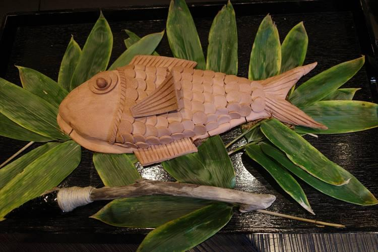 <strong>古墳時代</strong></br>金目鯛は縄文時代に行われていた粘土を使った蒸し焼きに着想を得た。金目鯛は朴葉で包んだ後、縄文土器を思わせる赤土の粘土で、ポール・ボキューズ氏のシグネチャーを思わせる魚の形に仕上げ、焼き上げた。
