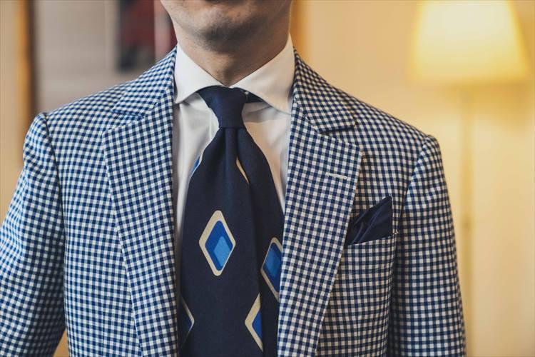 ふわりとスカーフのような雰囲気のタイ。存在感を強調するノットをずらした結び方が印象的だ。