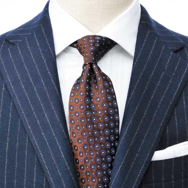 """<strong>10.悩み無用の織りストライプ</strong><br />それでもストライプシャツが苦手なら、どんなスーツやネクタイも似合う織りストライプの白シャツから始めよう。スーツは紺系、ネクタイは茶系で、イタリア男の定番配色""""アズーロ エ マローネ""""に則っている。"""