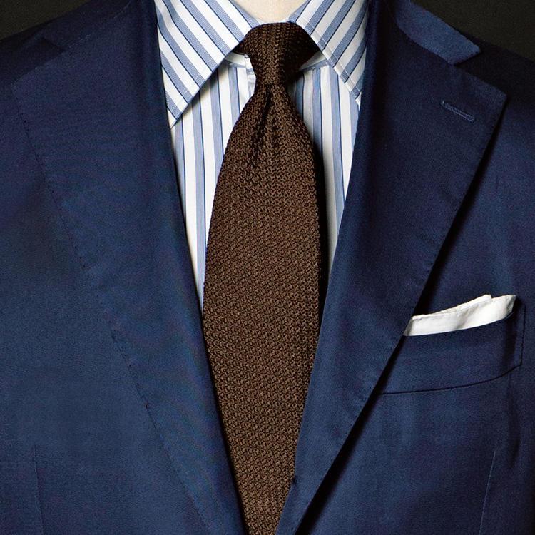 <strong>7位<br />紺スーツが簡単にきちんと見える、色合わせの法則とは?</strong><br />シンプルな紺無地スーツを、誰でも簡単にきちんと見せる色合わせのコツは? それが「紺×茶」の組み合わせだ。イタリアでは「アズーロ エ マローネ」(アズーロは紺、マローネは茶)と呼ばれ、ビジネスマンのスーツスタイルの鉄板配色として実践されている。紺スーツに対してブラウン無地のネクタイをもってくるだけでまとまりが出るが、さらに洒落度を高めるなら、白シャツでなくストライプなど柄モノのシャツを取り入れるのが◎。真面目さを保つなら、シャツのストライプもスーツと同系色のブルー系でまとめるのがよいだろう。<small>(2019年4月号掲載)</small>