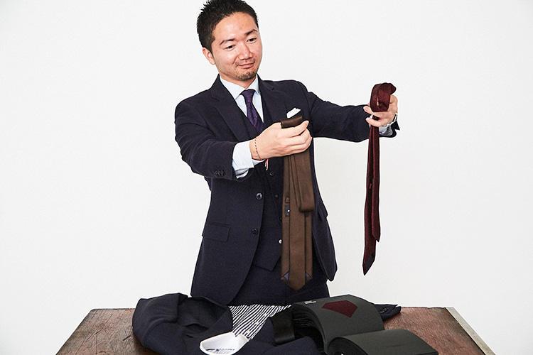 <strong>「ネクタイは細身のほうがモダンかな?」</strong><br />お次はネクタイを選ぶ。生地はもちろん、長さやシェイプも選ぶことができる。スーツが構築的でクラシックな分、若さも出したいので、剣幅7cmの細身ネクタイをセレクト。